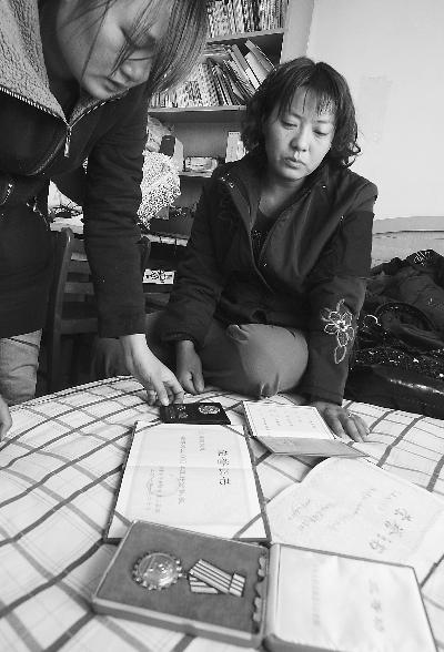 图为兰建国的妻子看着他生前的荣誉证书