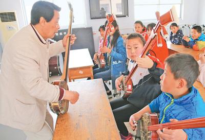 """学唱大鼓 《 人民日报 》( 2017年03月22日   12 版)        21日,在山东省惠民县胡集镇中心小学,河北民间艺人王金升正在教孩子们弹唱西河大鼓。从今年新学期开始,胡集镇各个小学的学生,都能在学校跟着民间艺人学习传统曲艺。胡集镇今年在全镇所有小学开展了""""书会进校园""""活动,邀请高水平艺人进校授课,给孩子们讲解西河大鼓等曲艺的历史和唱腔发音。据悉,胡集镇有着悠久的曲艺传统和观众基础,胡集书会更是首批国家级非物质文化遗产,每年都会吸引大量民间艺人来此献艺,迄今已有800余年历史。    本报 - weicuibai65 - 雕龙绣凤"""