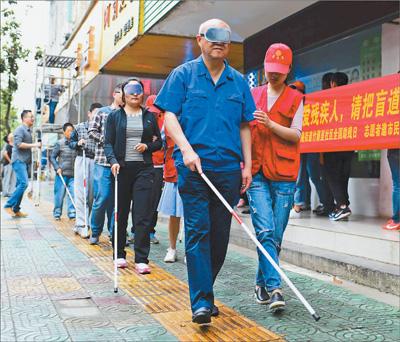 安徽合肥志愿者邀请市民体验盲道行走
