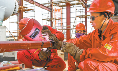 7月8日,在塔中凝析油稳定工程施工现场,工人在高温中焊接管线,确保