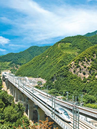 图为动车组穿行位于陕甘交界的秦岭山脉东岔车站.