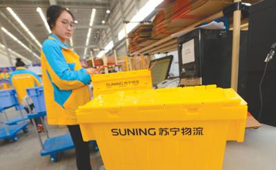 """某电商平台物流工作人员正在使用""""共享快递盒""""分装商品."""