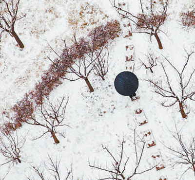 2月14日,一名河北邯郸市市民从雪中花园穿过.  乔海龙摄(新华社发)