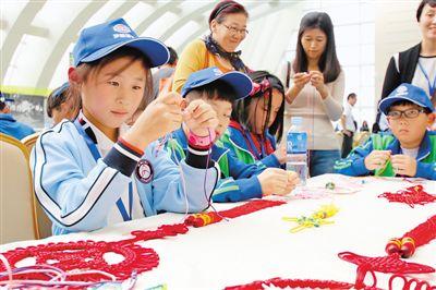 """妇女儿童博物馆参加了""""儿童非遗手工课堂""""体验活动,编织中国结手环"""