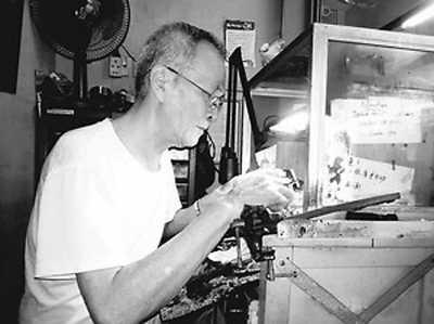 发、身材瘦削的老人,正低着头透 他熟练地用螺丝起子打开表盖,眯图片