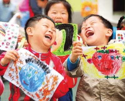 """幼儿园的小朋友展示自己的笑脸主题画作,迎接5月8日""""世界微笑日""""的到"""