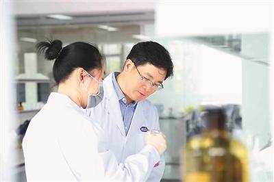 图为丁列明在实验室指导研发人员开展实验.